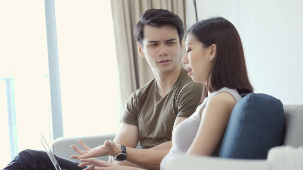 Upset husband argues with wife Upset young Asian man gestures while arguing with his wife. They are looking at their credit card statement online. They are using a laptop. asian couple arguing stock pictures, royalty-free photos & images