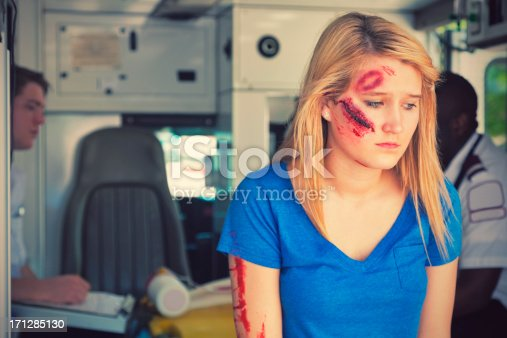 istock Upset injured young woman in ambulance looking down 171285130