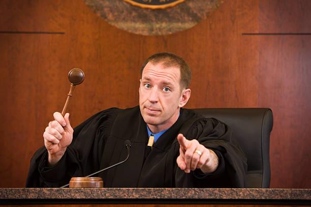 Upset judge swinging gavel and pointing stock photo