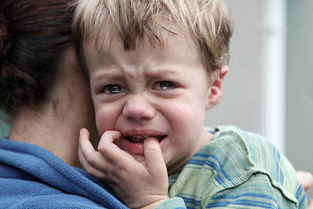 Upset little boy Upset little boy getting a hug. Desaturated desaturated stock pictures, royalty-free photos & images