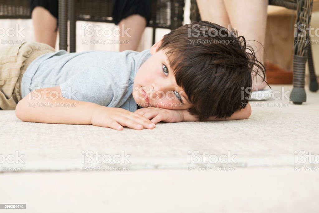 Upset Little Boy Throws Tantrum and Lays Down on Floor stock photo