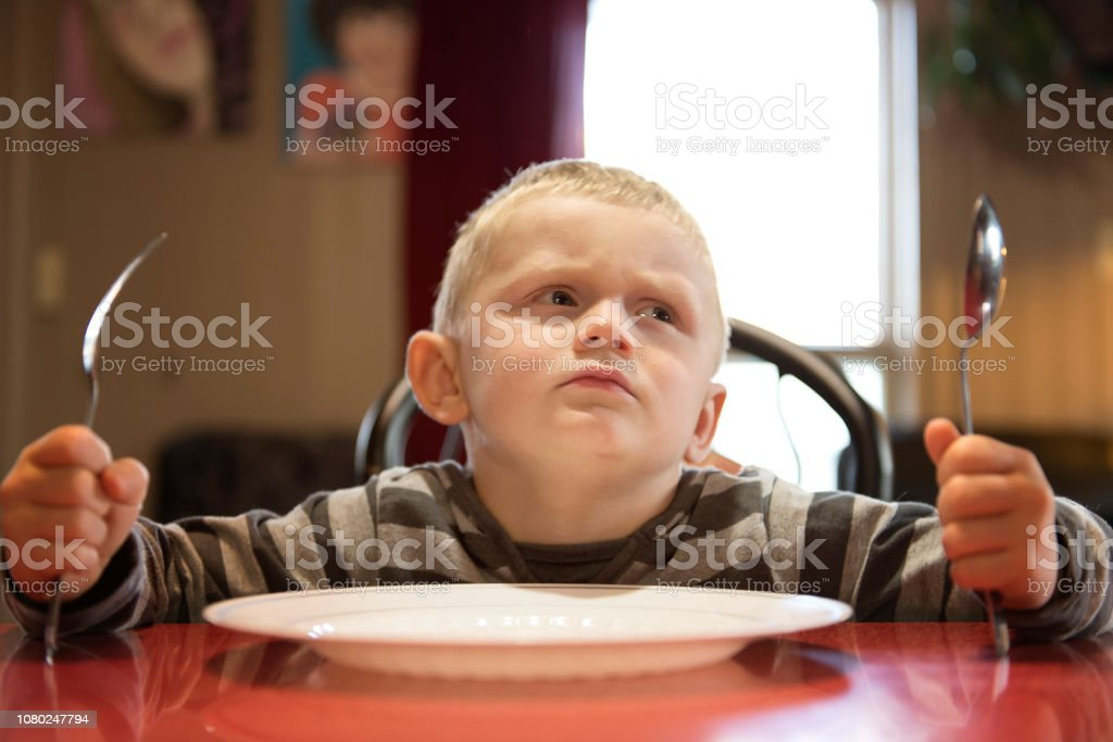 A Upset little boy waiting for dinner while holding a fork and a spoon Upset little boy waiting for dinner while holding a fork and a spoon 4-5 Years Stock Photo