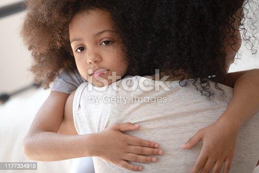 1135353632 istock photo Upset little cute mixed race girl hugging mom. 1177334915