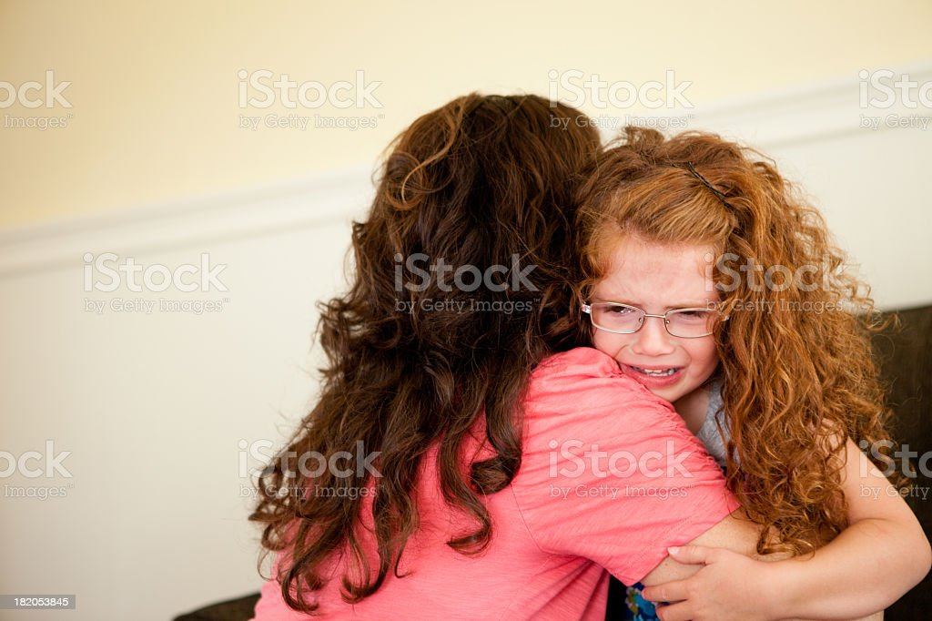 Upset Little Girl Crying in Her Mother's Arms royalty-free stock photo