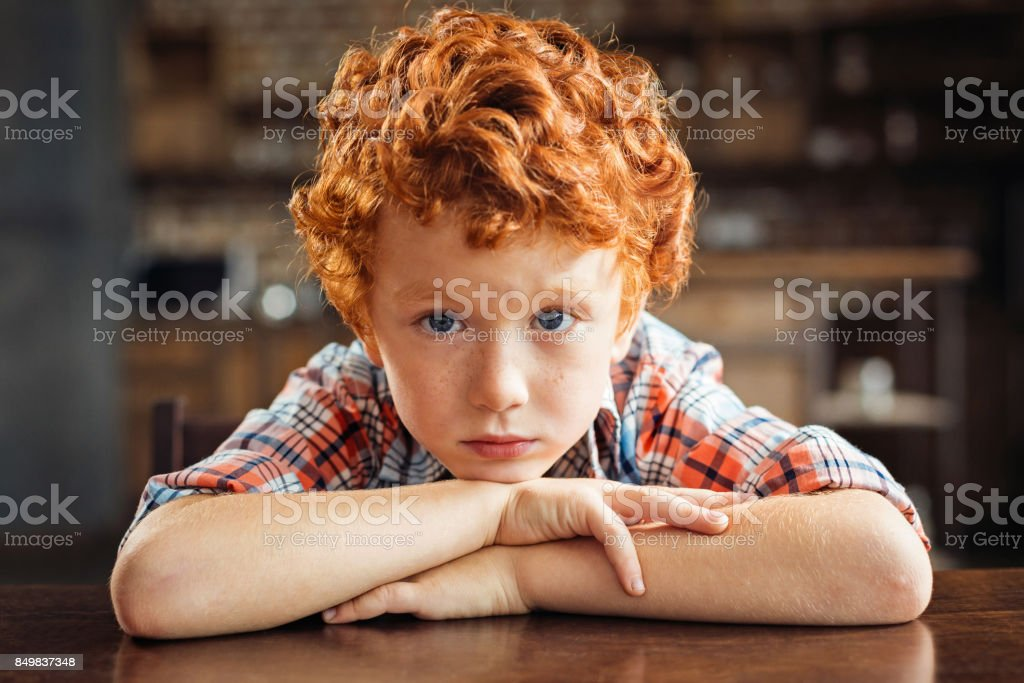 Upset little kid resting his chin on his folded arms stock photo