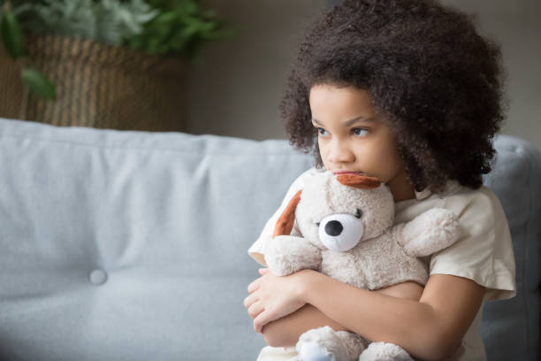 Upset lonely african kid girl holding teddy bear looking away stock photo