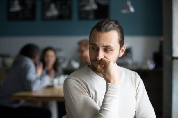 upset male outcast feel lonely sitting alone in cafe - disbarment stock pictures, royalty-free photos & images