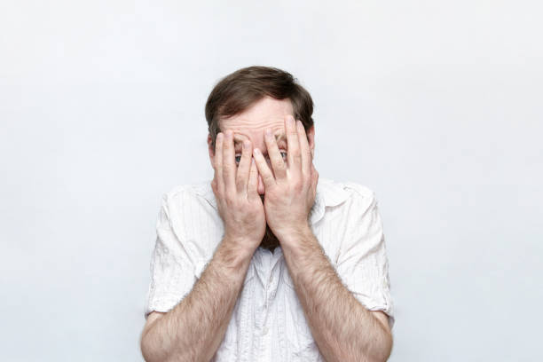 Upset man covering his face over gray background stock photo