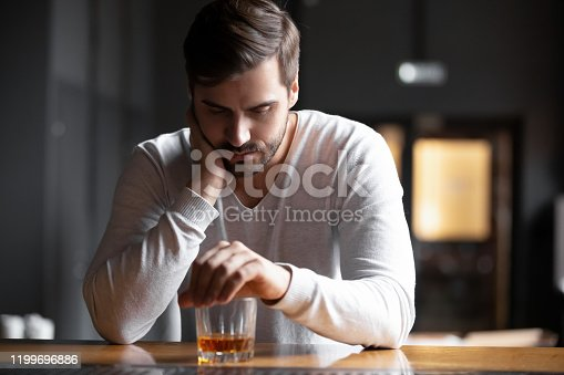 Upset young man drinker alcoholic sitting at bar counter with glass drinking whiskey alone, sad depressed addicted drunk guy having problem suffer from alcohol addiction abuse, alcoholism concept
