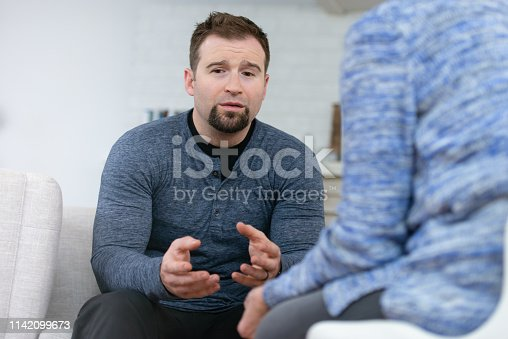 istock Upset man in therapy 1142099673
