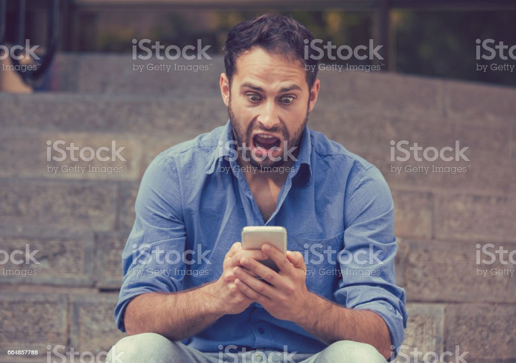 Upset man looking at his mobile phone sitting on steps outdoors foto de stock libre de derechos