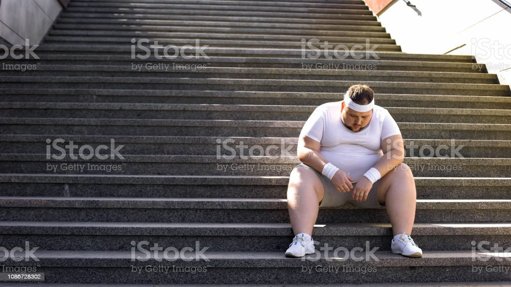 Aufgeregt Mann sitzt allein auf Treppen, kämpfen mit Übergewicht und Essen sucht – Foto