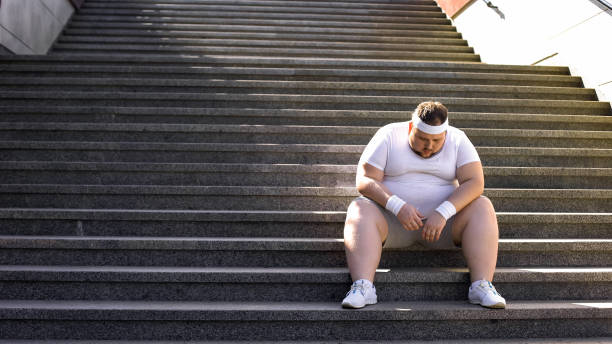 upset man sitting alone on stairs, fighting with overweight and food addiction - uomo stanco foto e immagini stock