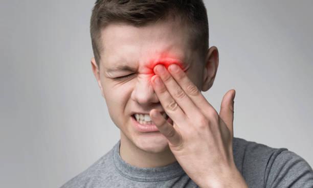 hombre molesto que sufre de fuerte dolor en los ojos - física fotografías e imágenes de stock