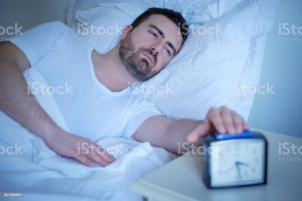 Molesto el hombre tratando de dormir en su cama por la noche - foto de stock