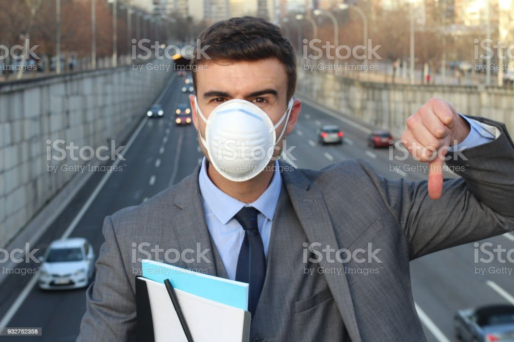 Upset man wearing a breathing mask giving stock photo