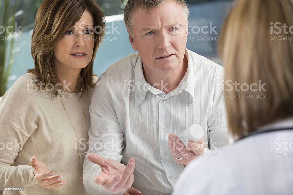 Upset mature couple with doctor and medicine royalty-free stock photo