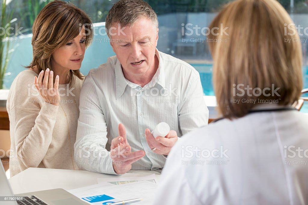 Upset mature couple with doctor and medicine stock photo