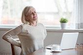 istock Upset mature woman sitting feeling back pain massaging aching muscles 1049512832