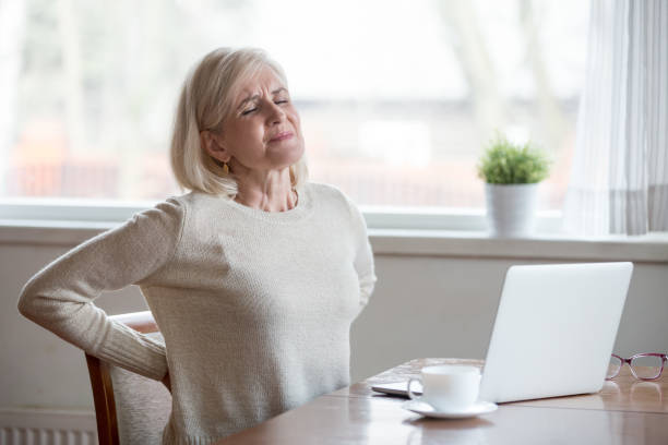 Upset mature woman sitting feeling back pain massaging aching muscles Upset mature middle aged woman feels back pain massaging aching muscles, sad senior older lady suffers from low-back lumbar pain sitting in incorrect sedentary posture, backache radiculitis concept back pain stock pictures, royalty-free photos & images
