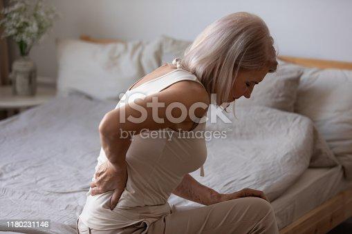 istock Upset mature woman suffering from backache, rubbing stiff muscles 1180231146