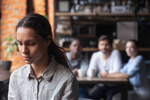 upset mixed race woman suffering from bullying, sitting alone in cafe - disbarment stock pictures, royalty-free photos & images