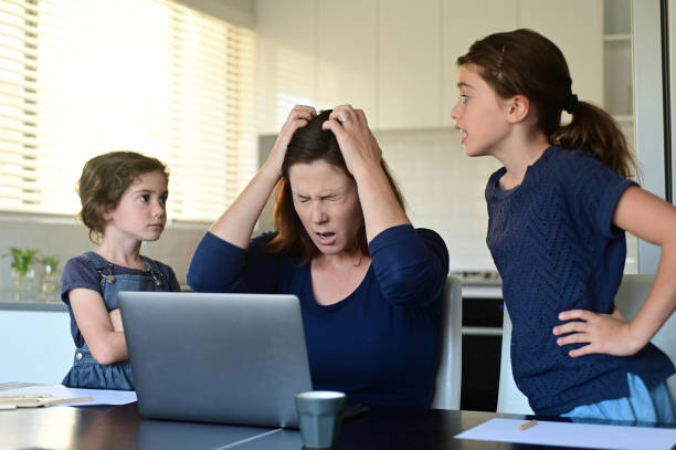 Upset mother forced to work from home as the pandemic coronavirus (COVID-19) forces many employees to work from home. stock photo