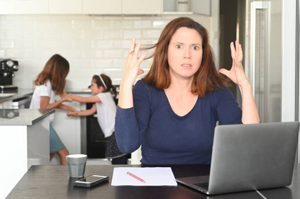 Upset mother working from home stock photo