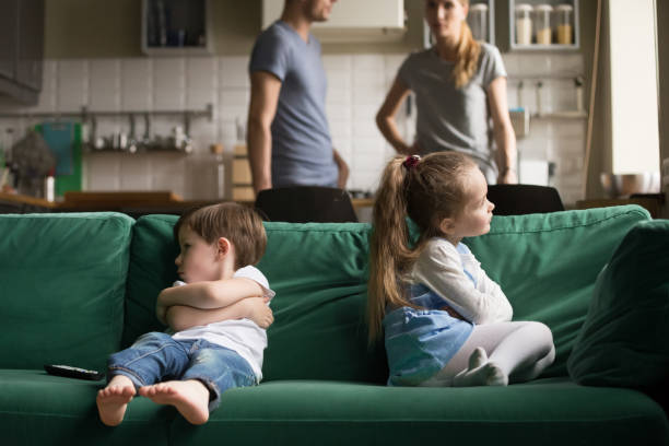 Upset offended brother and sister sitting on couch Upset offended toddler brother and sister sitting separately on couch, sofa with arms crossed, little girl and boy ignoring each other, not talking, puzzled parents discuss situation brother stock pictures, royalty-free photos & images