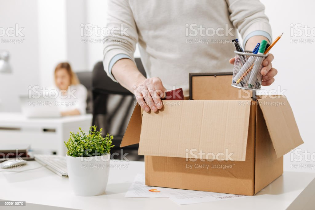 Upset office manager packing the box and leaving the office stock photo