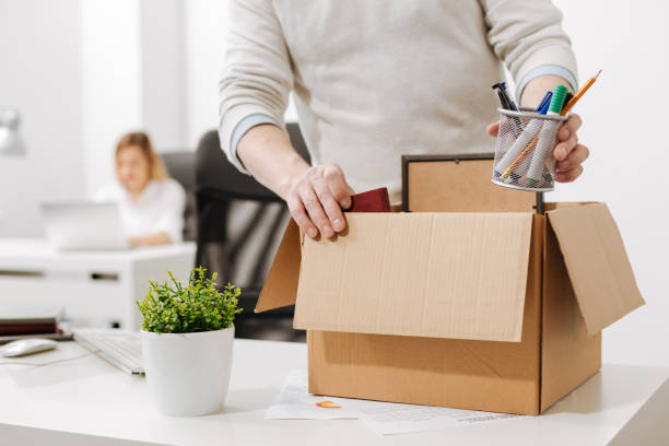 Upset office manager packing the box and leaving the office Taking a gap. Concentrated involved melancholy employee standing and packing the box with his belongings while leaving the company and expressing sadness downsizing unemployment stock pictures, royalty-free photos & images