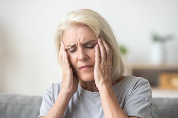 verärgert ältere frau berühren tempel schmerzenden kopf gefühl starke kopfschmerzen - schwindelig stock-fotos und bilder