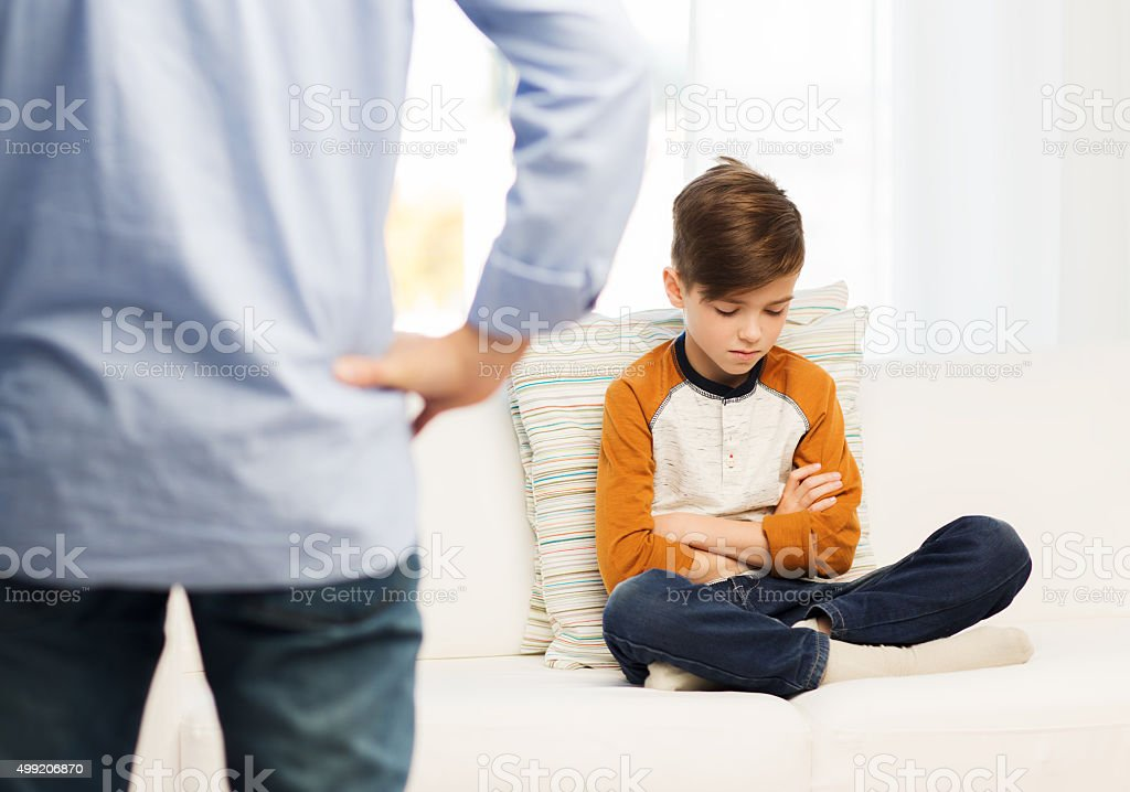 upset or feeling guilty boy and father at home stock photo