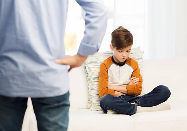 Verärgert oder nichtstuend herumliegend boy und Vater wie zu Hause fühlen. – Foto
