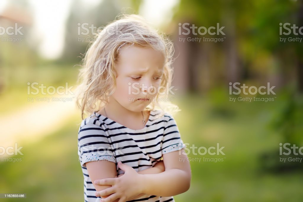 Upset or offended little girl standing on street of small town\'s or...