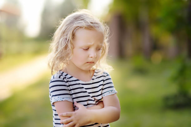 Upset or offended little girl standing on street of small town's or village's. risis of three years. stock photo