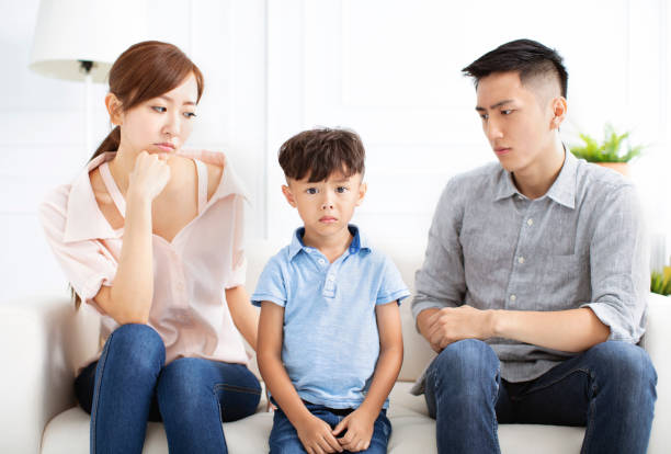 Upset parent and little boy sitting on sofa Upset parent and little boy sitting on sofa asian couple arguing stock pictures, royalty-free photos & images