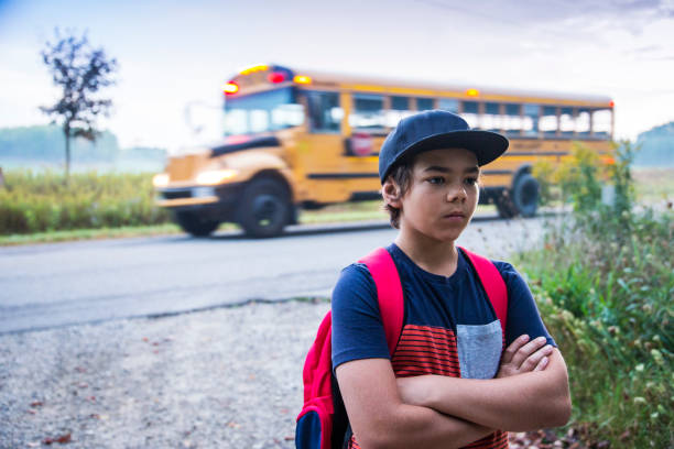 Upset preteen boy not wanting to go to school An upset, grumpy preteen boy resisting getting on the school bus in the morning. absentee stock pictures, royalty-free photos & images