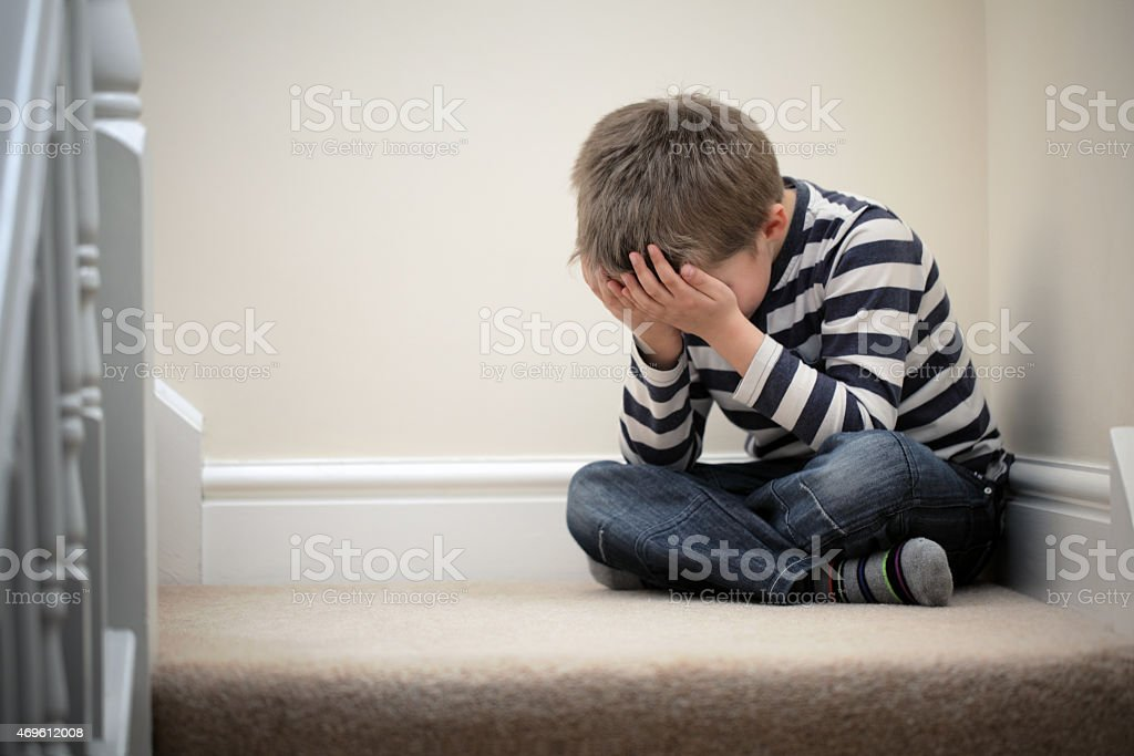 Upset problem child sitting on staircase stock photo