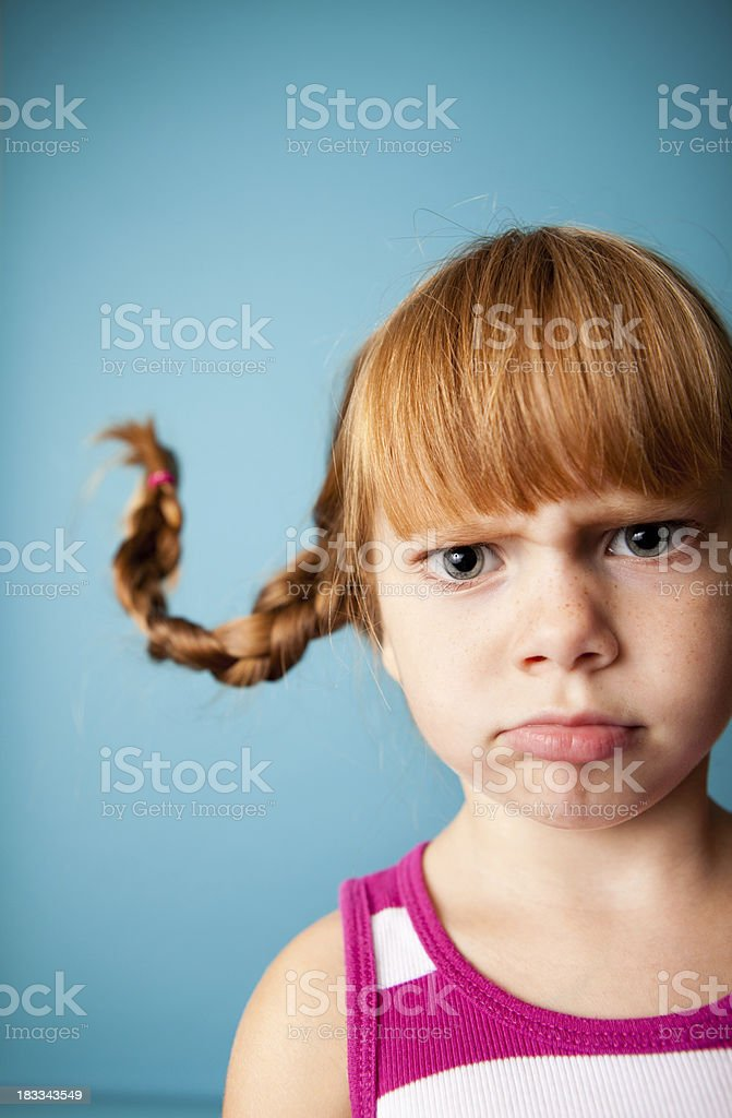 Upset Red-Haired Girl Pouting with Upward Braids stock photo