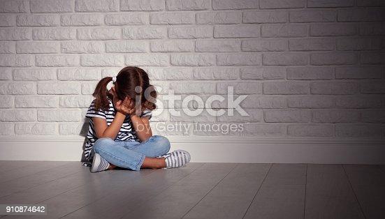 istock upset sad sad child girl in stress cries at an empty dark wall 910874642