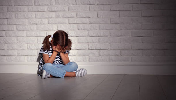 upset sad sad child girl in stress cries at an empty dark wall - one girl only stock pictures, royalty-free photos & images