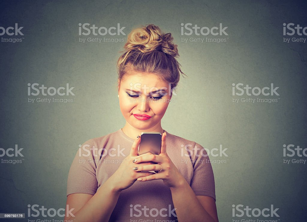 upset sad skeptical woman talking texting on phone stock photo