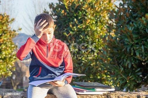 istock Upset sad teenager with textbooks and notebooks 1128015062