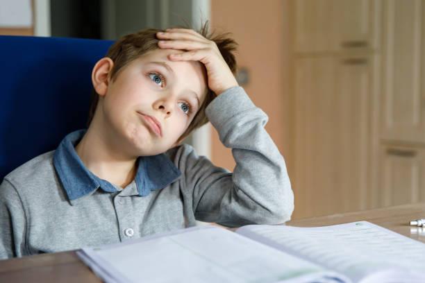 verstoorde schooljongen die thuis werk tijdens quarantainetijd van corona pandemieziekte maakt. huilende en droevige jongen frustrerend thuis blijven. - tears corona stockfoto's en -beelden
