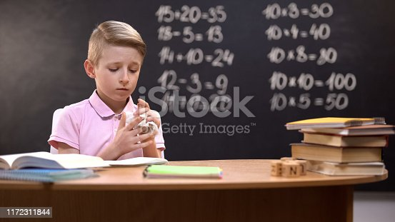 istock Upset schoolboy crumpling page from notebook, unable to solve difficult task 1172311844