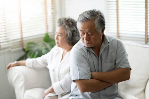 Upset Senior man sitting on sofa against the background of his wife. stock photo