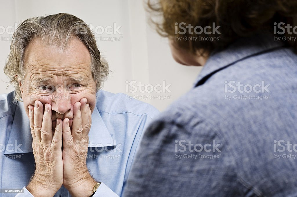 Upset senior man with hands on face at counseling session. royalty-free stock photo