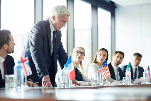 Upset senior politician talking at meeting Upset displeased senior politician in suit standing up and talking about his position loudly at meeting, government representatives attentively listening to him diplomacy stock pictures, royalty-free photos & images