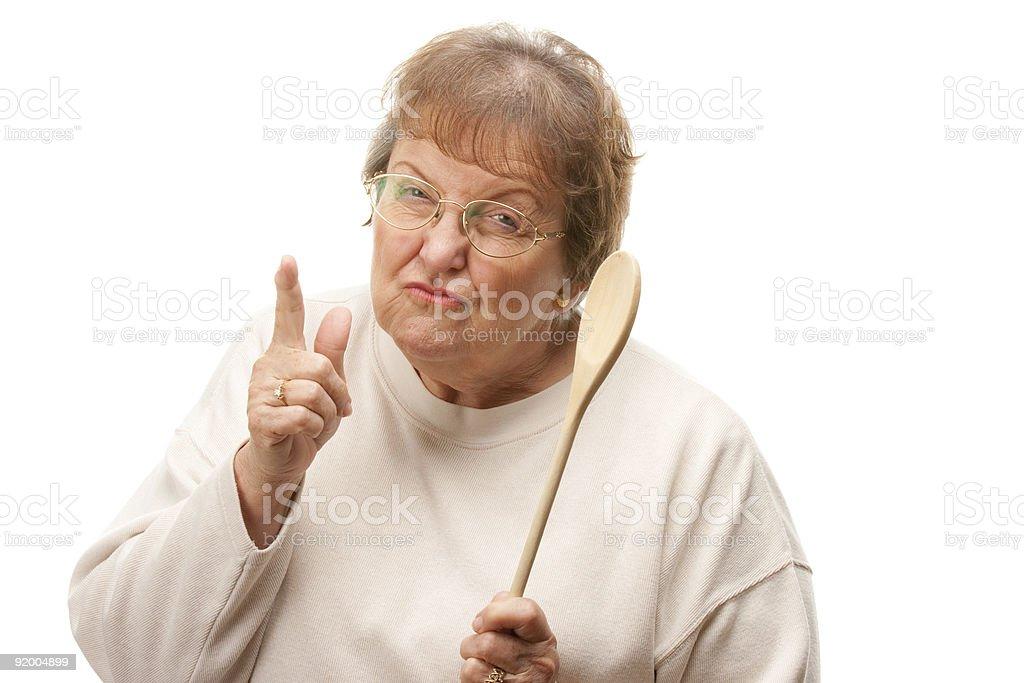 Upset Senior Woman with The Wooden Spoon stock photo
